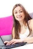 Muchacha feliz del estudiante que usa la computadora portátil Imagen de archivo
