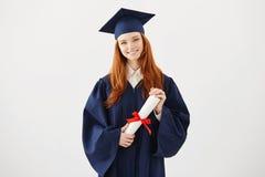 Muchacha feliz del graduado del jengibre en casquillo y capa que sonríen sosteniendo el diploma Copie el espacio Imagen de archivo
