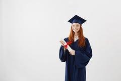 Muchacha feliz del graduado del jengibre en casquillo y capa que sonríen sosteniendo el diploma Copie el espacio Imagen de archivo libre de regalías