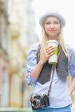 Muchacha feliz del inconformista con la taza de bebida caliente en la calle de la ciudad Fotografía de archivo
