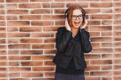 Muchacha feliz del inconformista con los auriculares en fondo de la pared de ladrillo Fotografía de archivo