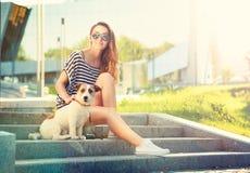 Muchacha feliz del inconformista con su perro en la ciudad Foto de archivo