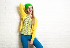 Muchacha feliz del inconformista en el fondo blanco de la pared de ladrillo Foto de archivo