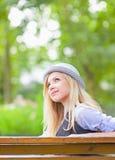 Muchacha feliz del inconformista en el sombrero que se sienta en banco en el parque Imagen de archivo libre de regalías
