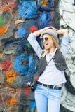 Muchacha feliz del inconformista que mira en espacio de la copia contra la pared urbana Foto de archivo