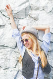 Muchacha feliz del inconformista que presenta contra la pared rocosa al aire libre Imagen de archivo libre de regalías