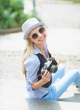 Muchacha feliz del inconformista que se sienta en las escaleras con la cámara retra de la foto Fotografía de archivo