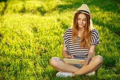 Muchacha feliz del inconformista que usa la tableta al aire libre Imágenes de archivo libres de regalías