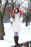 Muchacha feliz del invierno con dos corazones rojos que se colocan en banco Imagen de archivo libre de regalías