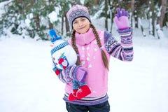 Muchacha feliz del invierno con la muñeca del muñeco de nieve Imagen de archivo