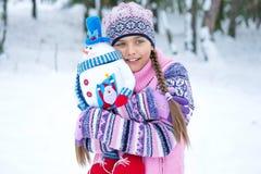 Muchacha feliz del invierno con la muñeca del muñeco de nieve Foto de archivo