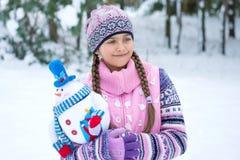 Muchacha feliz del invierno con la muñeca del muñeco de nieve Fotografía de archivo