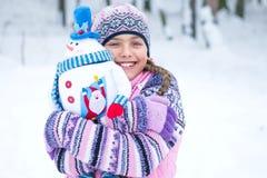 Muchacha feliz del invierno con la muñeca del muñeco de nieve Foto de archivo libre de regalías