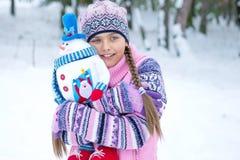 Muchacha feliz del invierno con la muñeca del muñeco de nieve Imagen de archivo libre de regalías