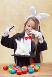 Muchacha feliz del mago que conjura encima del conejito y de los huevos de pascua Fotografía de archivo