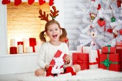 Muchacha feliz del niño con el regalo por mañana en el árbol de navidad fotos de archivo