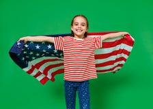 Muchacha feliz del niño con la bandera de los Estados Unidos de América los E.E.U.U. en fondo verde fotografía de archivo
