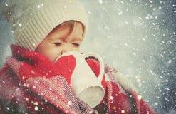 Muchacha feliz del niño con la taza de bebida caliente en invierno frío al aire libre Imagenes de archivo