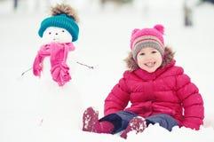 Muchacha feliz del niño con un muñeco de nieve en un paseo del invierno Fotos de archivo