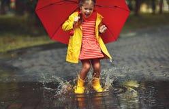 Muchacha feliz del niño con un paraguas y botas de goma en charco encendido imagenes de archivo