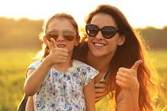 Muchacha feliz del niño de la moda que abraza a su madre en gafas de sol de moda Fotografía de archivo