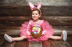 Muchacha feliz del niño del trasero en traje del conejito de pascua con los huevos Imágenes de archivo libres de regalías