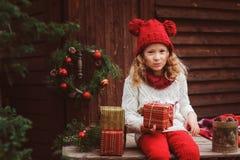 Muchacha feliz del niño en sombrero rojo y la bufanda que envuelven los regalos de la Navidad en la casa de campo acogedora, ador Fotografía de archivo libre de regalías