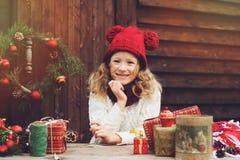Muchacha feliz del niño en sombrero rojo y la bufanda que envuelven los regalos de la Navidad en la casa de campo acogedora, ador Imagenes de archivo