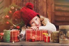 Muchacha feliz del niño en sombrero rojo y la bufanda que envuelven los regalos de la Navidad en la casa de campo acogedora, ador Foto de archivo libre de regalías