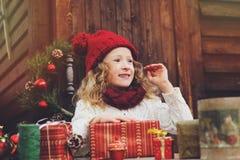 Muchacha feliz del niño en sombrero rojo y la bufanda que envuelven los regalos de la Navidad en la casa de campo acogedora, ador Fotografía de archivo