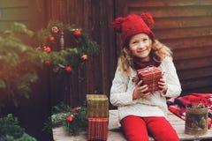 Muchacha feliz del niño en sombrero rojo y la bufanda que envuelven los regalos de la Navidad en la casa de campo acogedora, ador Fotos de archivo