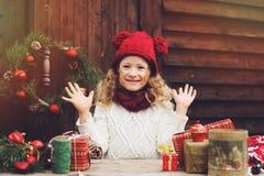 Muchacha feliz del niño en sombrero rojo y la bufanda que envuelven los regalos de la Navidad en la casa de campo acogedora, ador Imagen de archivo