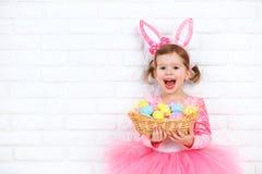 Muchacha feliz del niño en un conejo de conejito de pascua del traje con la cesta de Foto de archivo libre de regalías