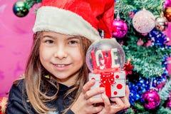 Muchacha feliz del niño en un sombrero de la Navidad que sostiene el regalo de cristal del globo de Foto de archivo