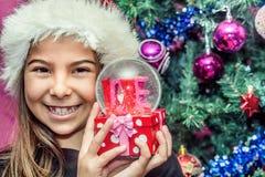 Muchacha feliz del niño en un sombrero de la Navidad que sostiene el regalo de cristal del globo de Fotos de archivo