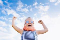 Muchacha feliz del niño hermoso en gafas de sol con las manos abiertas contra imágenes de archivo libres de regalías