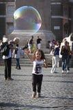 Muchacha feliz del niño que corre hacia una burbuja de jabón Foto de archivo libre de regalías