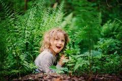 Muchacha feliz del niño que juega y que oculta en helechos salvajes en bosque del verano Imagenes de archivo