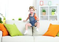 Muchacha feliz del niño que juega y que salta en el sofá en casa imagenes de archivo
