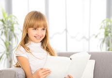 Muchacha feliz del niño que lee un libro mientras que se sienta en el sofá fotos de archivo