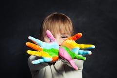 Muchacha feliz del niño que muestra sus manos de pintura coloridas en el retrato del fondo de la pizarra de la sala de clase imagen de archivo libre de regalías