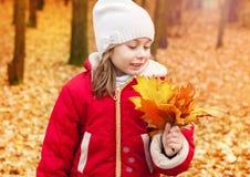 Muchacha feliz del niño que recoge las hojas en un parque del otoño Foto de archivo