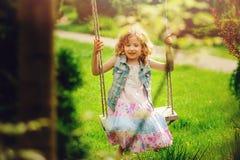 Muchacha feliz del niño que se relaja en el oscilación en jardín de la primavera Imagen de archivo