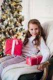 Muchacha feliz del niño que se sienta en la butaca cubierta con una manta contra la chimenea adornada de la Navidad Imágenes de archivo libres de regalías