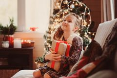 Muchacha feliz del niño que sostiene el regalo por la Navidad o el Año Nuevo en casa Foto de archivo libre de regalías
