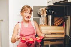 Muchacha feliz del niño que sostiene la bandeja de molletes recientemente cocidos imagenes de archivo