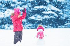 Muchacha feliz del niño con un muñeco de nieve en un paseo del invierno Imagen de archivo