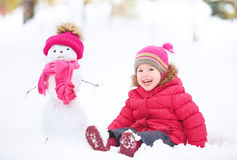Muchacha feliz del niño con un muñeco de nieve en un paseo del invierno Fotos de archivo libres de regalías