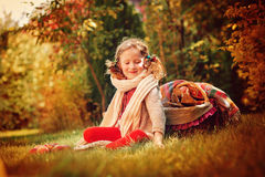 Muchacha feliz del niño en la bufanda caliente que se sienta con las manzanas en jardín del otoño Imágenes de archivo libres de regalías