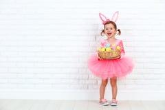 Muchacha feliz del niño en un conejo de conejito de pascua del traje con la cesta de Fotos de archivo libres de regalías